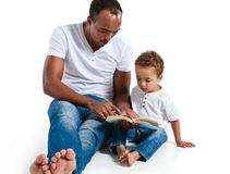 Father and son reading a book. Careful dad helping child to learn new things Royalty Free Stock Image