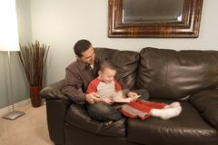 Father and Son Reading a Book on the Couch. Father is reading a book to his hyper son moving around stock photos