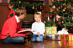 Father and son reading book by fireplace Royalty Free Stock Photo
