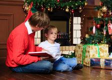 Father and son reading book by fireplace Royalty Free Stock Photos