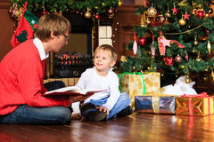 Father and son reading book by fireplace Royalty Free Stock Images