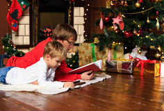 Father and son reading book by fireplace Royalty Free Stock Image