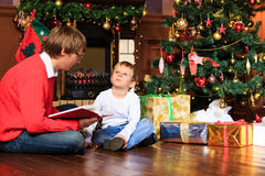 Father and son reading book by fireplace Stock Photos