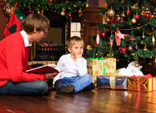 Father and son reading book by fireplace Royalty Free Stock Photography