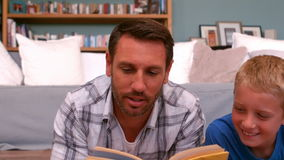 Father and son reading book stock footage