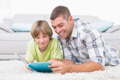 Father and son reading book while lying on floor Stock Photos
