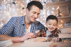 Father and son are reading book with magnifier at night at home. Father and son are reading book with magnifier at table at night at home Royalty Free Stock Photos