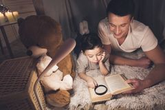 Father and son are reading book with magnifying glass at night at home. Father and son are reading book with magnifying glass in blanket fort at night at home Stock Images