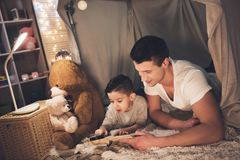 Father and son are reading book with magnifying glass at night at home. Father and son are reading book with magnifying glass in blanket fort at night at home Stock Photos