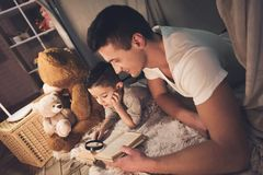 Father and son are reading book with magnifying glass at night at home. Father and son are reading book with magnifying glass in blanket fort at night at home Royalty Free Stock Photos