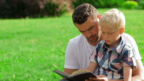 Father and son reading book stock video