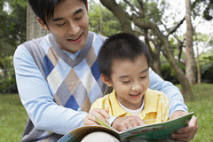 Father And Son Reading Book In Park. Happy father and son reading book in park Royalty Free Stock Images