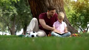 Father and son reading book in park, man encourages boy to knowledge, family. Father and son reading book in park, men encourages boy to knowledge, family, stock stock photo
