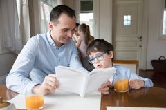Father and son reading book together at dining room royalty free stock photo