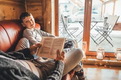 Father and son reading book together lying on the cozy sofa in warm country house. Reading to kids conceptual image royalty free stock images