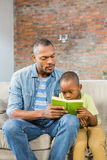 Father and son reading on the couch Stock Images
