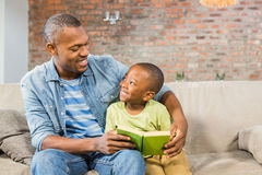 Father and son reading on the couch Stock Image