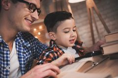 Father and son are reading fairy tales book with magnifying glass at night at home. Father and son are reading fairy tales book with magnifying glass at table Royalty Free Stock Photography