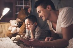 Father and son are reading fairy tales book at night at home. Father and son are reading fairy tales book in blanket fort at night at home Royalty Free Stock Images