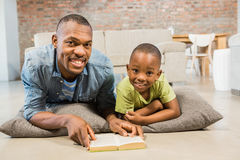 Father and son reading on the floor Royalty Free Stock Photo