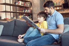 Father and son reading newspaper together Royalty Free Stock Image