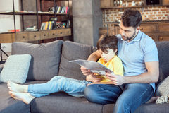 Father and son reading newspaper together at home. Focused father and son reading newspaper together at home Stock Image