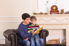 Father and son reading story book together.  Stock Photo