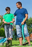 Father and son ready for some lawn mowing. And trimming stock photo