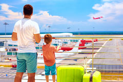 Father and son ready for summer vacation, while waiting for boarding in international airport. Father and son are ready for summer vacation, while waiting for stock photography