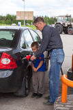 Father with son refueling car on gas station Stock Photos
