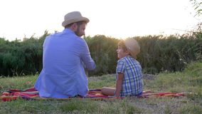 Father son relationship, dad with little boy in straw hats enjoy the sunset sitting on a blanket in open air. Father son relationship, dad with little boy in stock footage