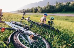 Father and son relax in green grass aftwr bicykle walk Stock Photo