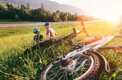 Father and son relax in green grass aftwr bicykle walk Stock Image