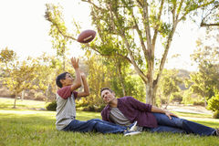 Father and son relax, throwing American football in a park stock images