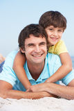 Father And Son Relaxing On Beach Holiday. Smiling At Camera royalty free stock photos