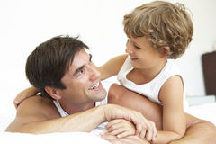 Father and Son relaxing on Bed together Royalty Free Stock Images