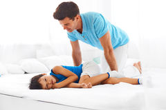 Father and son relaxing on bed together Stock Images