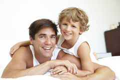 Father And Son Relaxing On Bede Together Stock Image