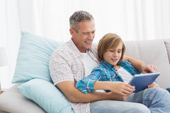 Father with son relaxing on the couch using laptop Stock Photo