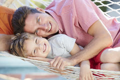 Father And Son Relaxing In Garden Hammock Together Stock Photo