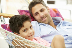 Father And Son Relaxing In Garden Hammock Together Royalty Free Stock Image