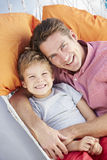 Father And Son Relaxing In Garden Hammock Together Royalty Free Stock Photo