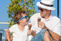 Father and son relaxing near a swimming pool at the day time. Stock Images