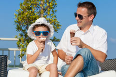 Father and son relaxing near a swimming pool at the day time. Royalty Free Stock Photography
