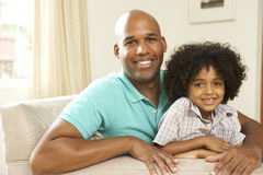Father And Son Relaxing On Sofa At Home Stock Photography
