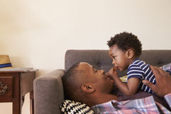Father And Son Relaxing On Sofa At Home Together stock photography