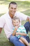Father And Son Relaxing In Summer Park Stock Photos