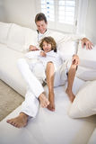 Father and son relaxing together on white sofa Stock Photo