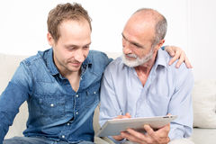Father and son remembering. Father and son looking at device Stock Photos