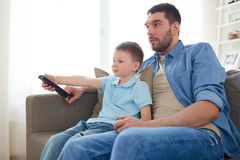 Father and son with remote watching tv at home Royalty Free Stock Image